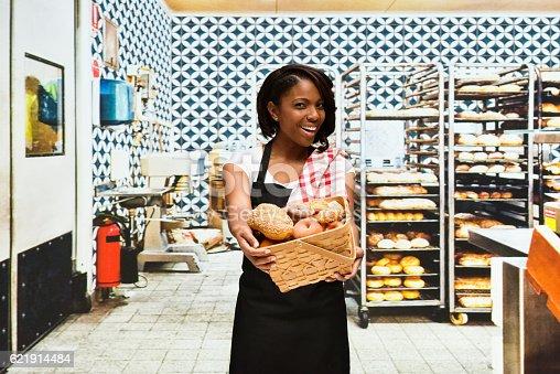 545282128 istock photo Smiling female baker holding basket in bakery 621914484