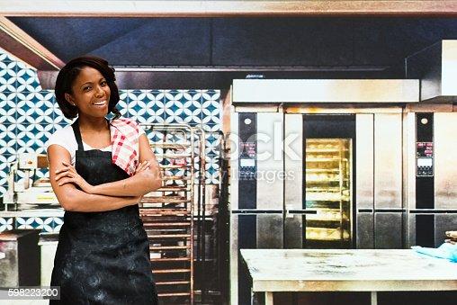 545282128 istock photo Smiling female baker standing in bakery 598223200