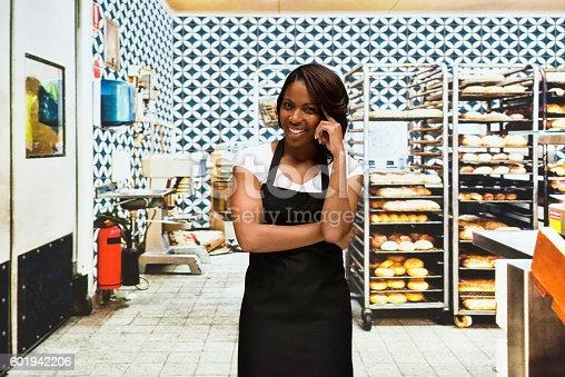 545282128 istock photo Smiling female baker standing in bakery 601942206