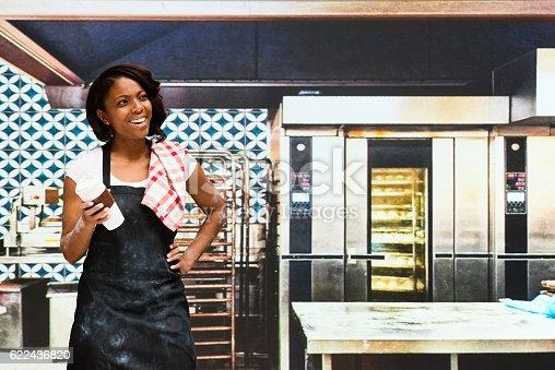 545282128 istock photo Smiling female baker standing in bakery 622436820