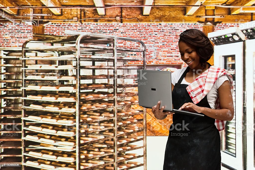 Smiling female baker working on laptop in bakery stock photo