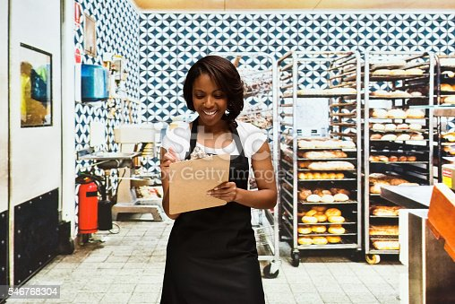 545282128 istock photo Smiling female baker writing on clipboard in bakery 546768304
