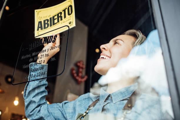 Smiling female barber hanging open sign on door stock photo