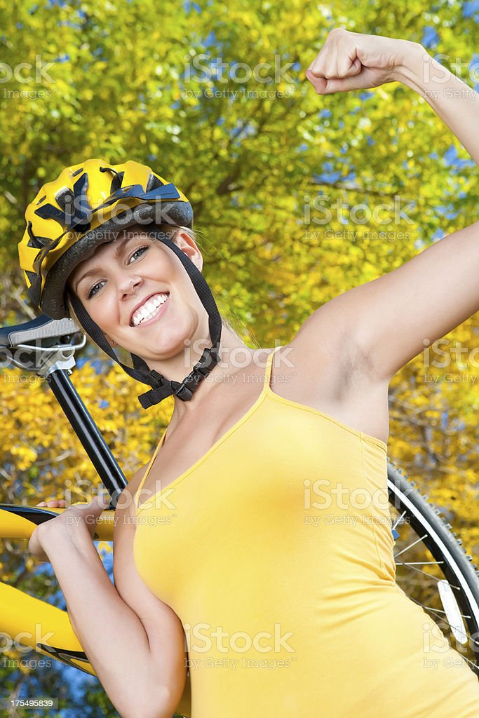 Smiling female biker lifting bike royalty-free stock photo