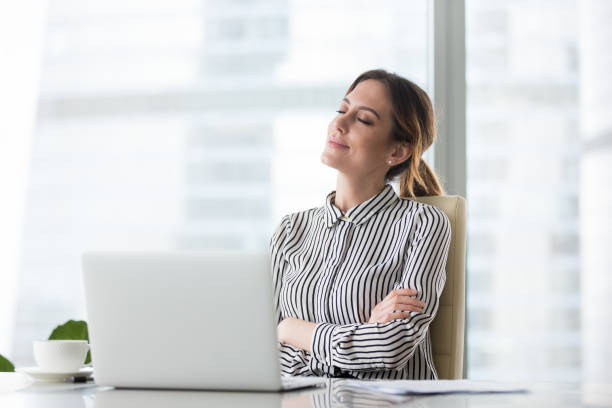 Smiling female boss relaxing in office chair with eyes closed Smiling businesswoman sitting in office chair relaxing with eyes closed, calm female worker or woman ceo feeling peaceful resting at workplace dreaming about positive things distracted from work day dreaming stock pictures, royalty-free photos & images