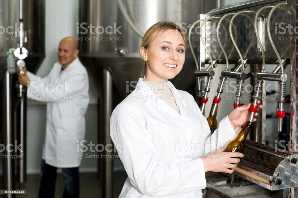 Smiling female brewery worker with bottling machinery stock photo
