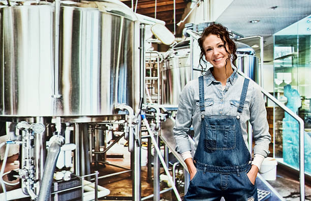 Smiling female brewmaster in industry stock photo