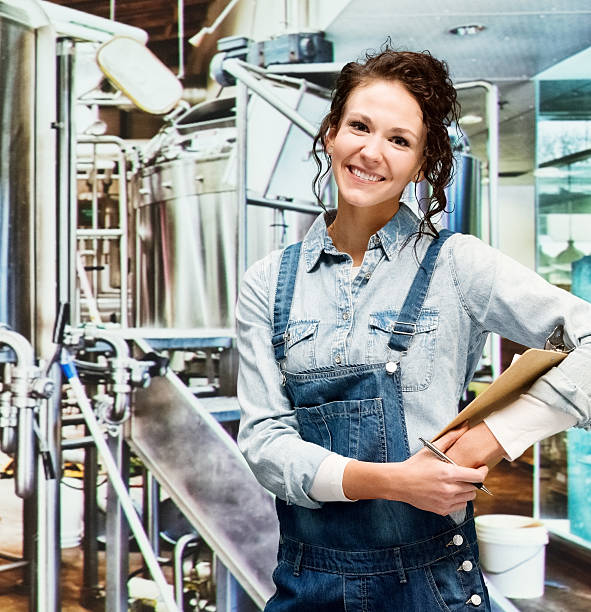 Smiling female brewmaster standing in brewery stock photo