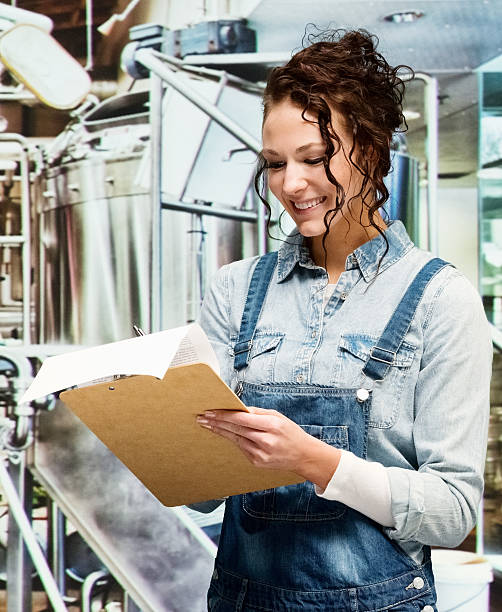 Smiling female brewmaster working at a brewery stock photo