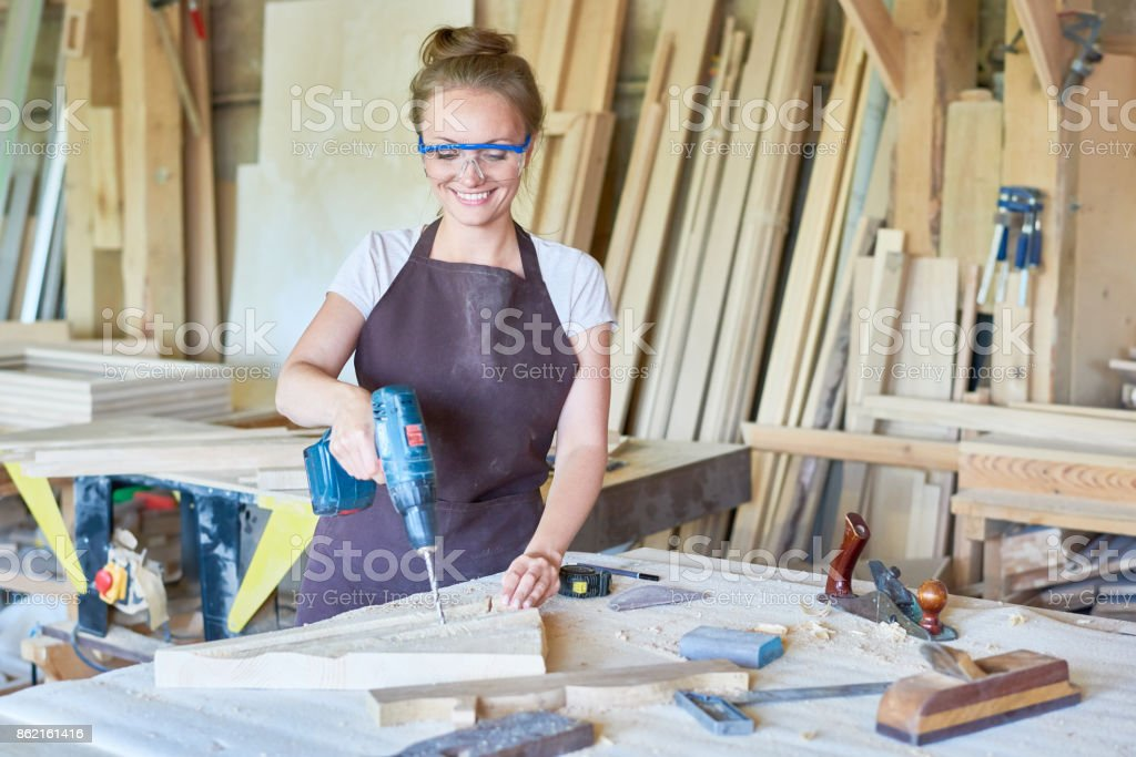 Smiling Female Carpenter Working in Shop stock photo
