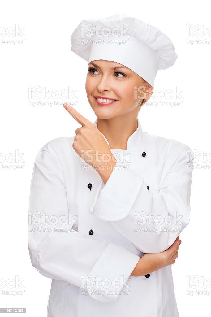 smiling female chef pointing finger to sonething stock photo