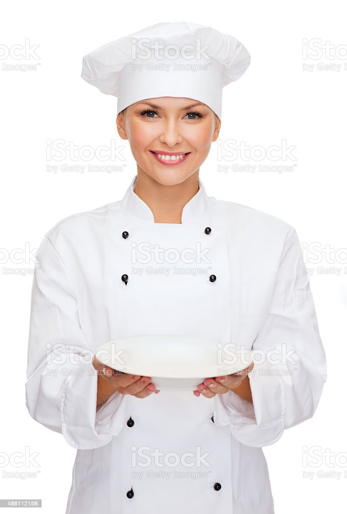 smiling female chef with empty plate stock photo