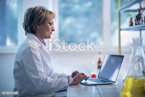 Mature forensic scientist working on the computer in a laboratory.