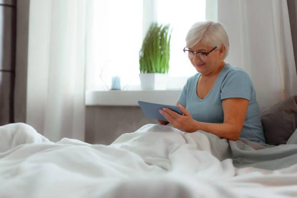 lächelnde frau klickt auf die tablette, während sie im bett liegt - sexy granny stock-fotos und bilder
