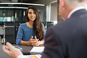 Portrait of young Indian female client or candidate sitting at table, talking to senior male manager and smiling in office. Job interview or consultancy concept
