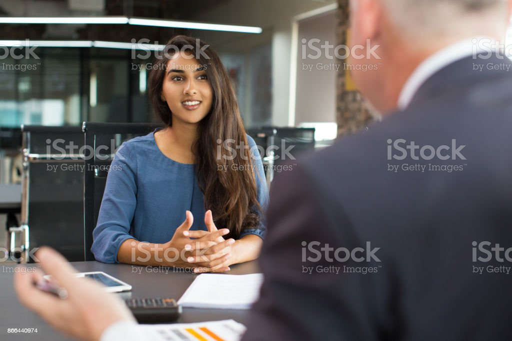 Smiling female client talking to male manager stock photo
