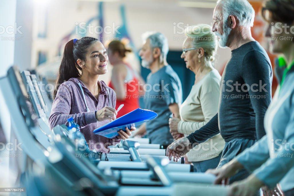 Smiling female coach talking to senior man on treadmill while making...