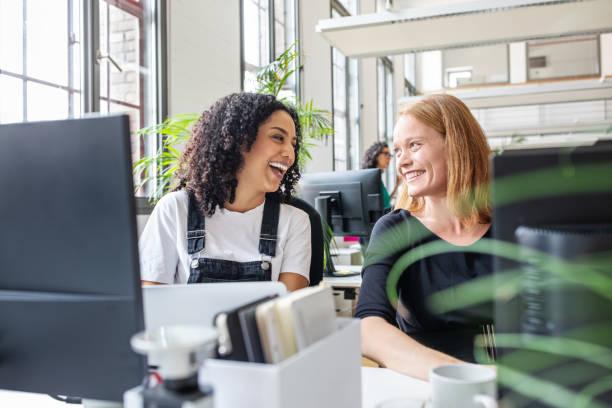 Lächelnde Kolleginnen arbeiten im Büro zusammen – Foto