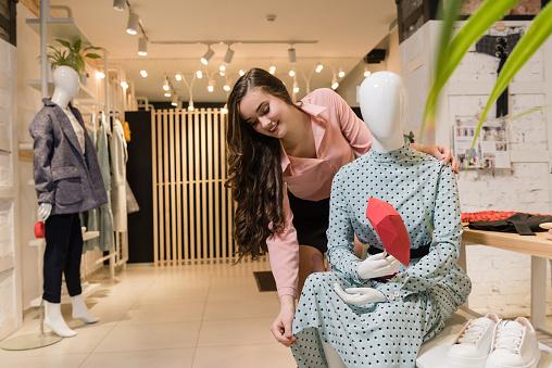 672064598 istock photo Smiling female consultant seller arrange clothing 1135185445