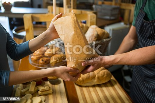 istock Smiling female customer receiving a parcel from bakery staff at counter 657289808