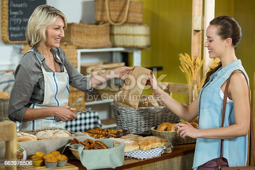 istock Smiling female customer receiving a parcel from bakery staff at counter 663978506