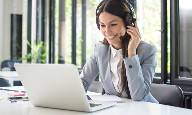 Smiling female customer support operator talking with client and using laptop in office stock photo