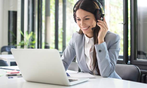 Lächelnde weibliche Kundenbetreuerin im Gespräch mit Dem Kunden und mit Laptop im Büro – Foto