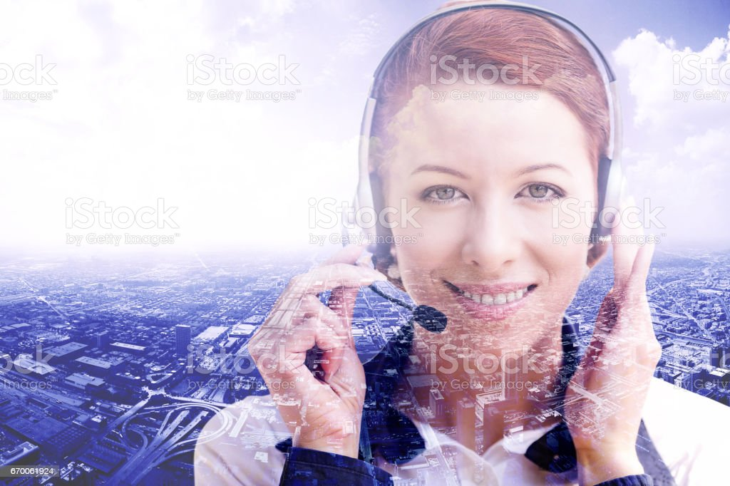 Smiling female customer support operator with headset isolated on cityscape background stock photo