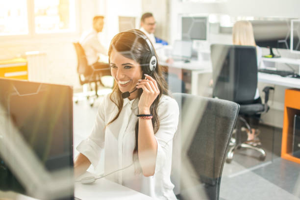 Smiling female customer support operator with headset working in office stock photo