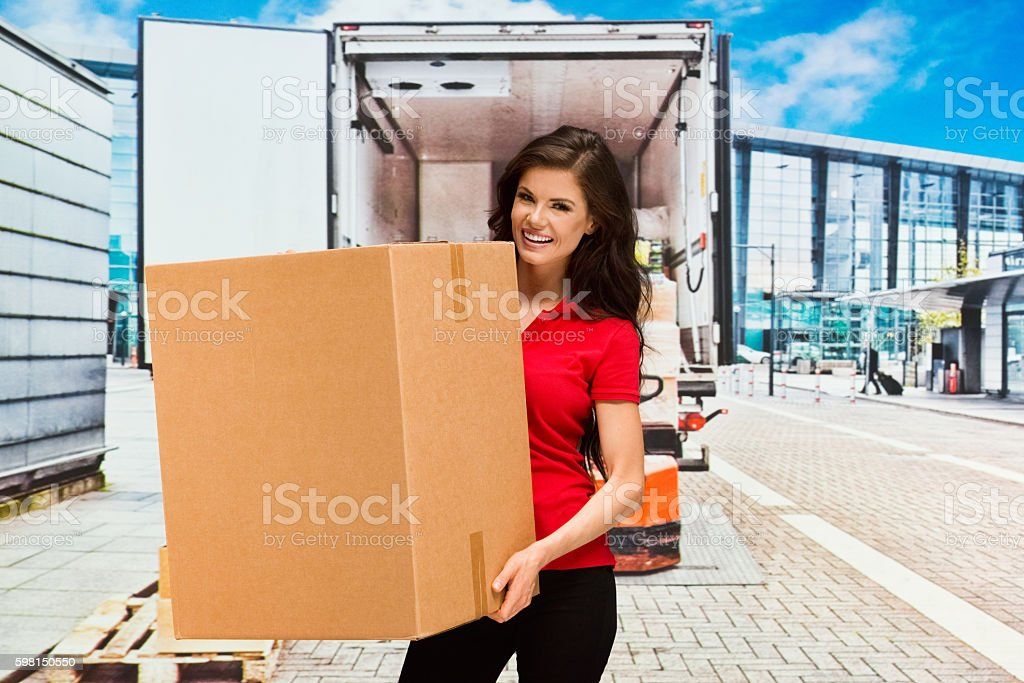 Smiling female delivery person working...