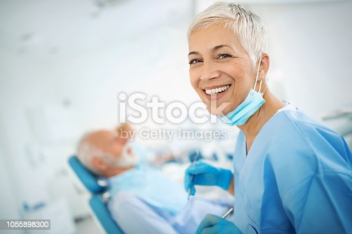 Closeup of a mid 50's female dentist proudly posing for the camera in her office. She's wearing blue scrubs and mask. Senior male patient is in the background.