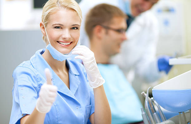 smiling female dentist - dental assistant stock photos and pictures