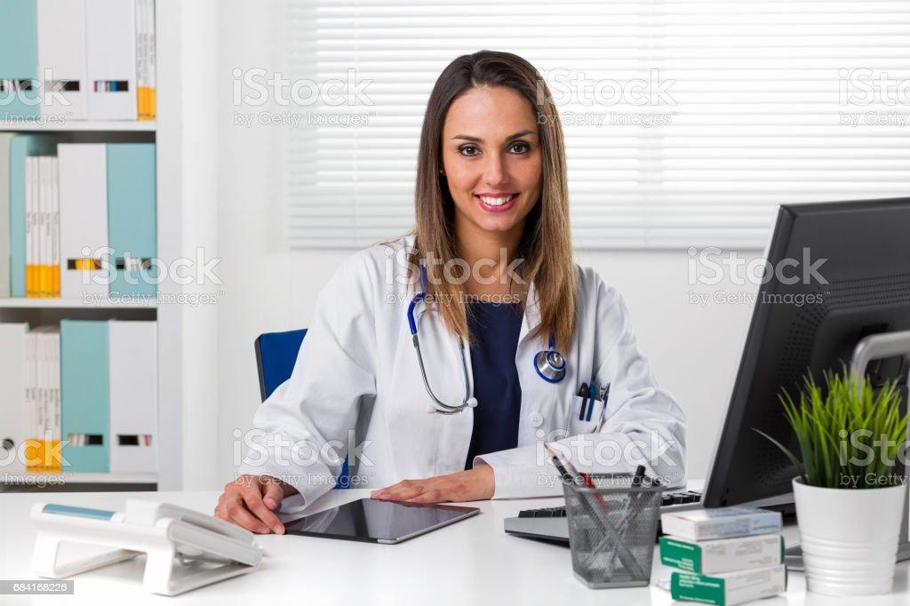 Smiling female doctor at desk using tablet photo libre de droits