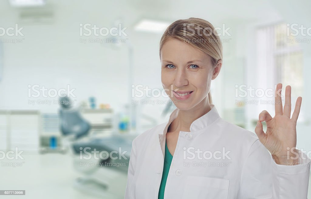 Smiling Female doctor dentist showing Ok or Alright Sign. stock photo
