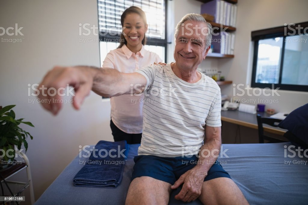 Smiling female doctor examining shoulder of senior male patient stock photo