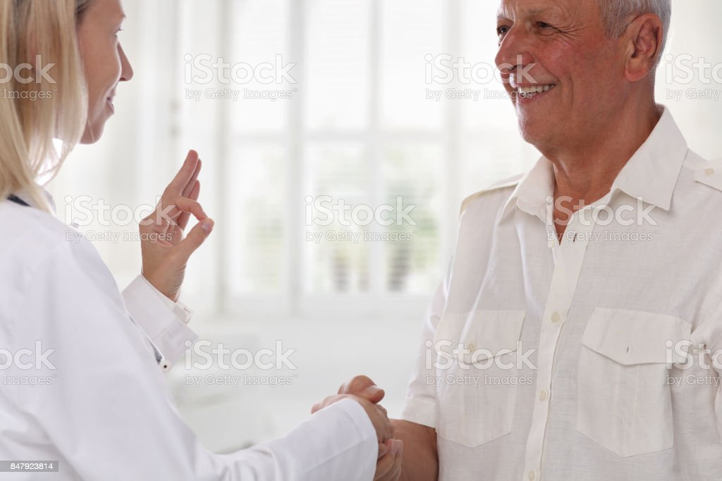 Smiling female doctor giving handshake to senior male patient and showing alright sign. Healthcare concept stock photo