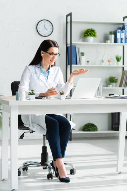 smiling female doctor having online consultation with patient on laptop in office stock photo