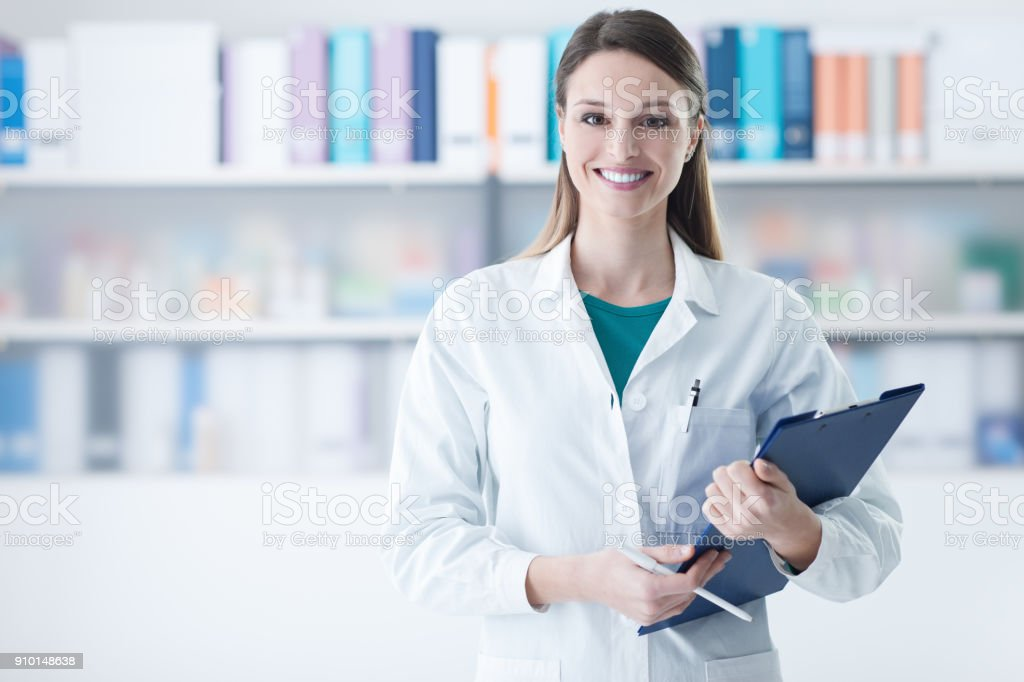 Smiling female doctor holding a clipboard stock photo