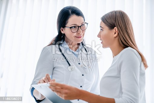 522625266istockphoto Smiling female doctor holding medical report and talking with female patient 1189208221