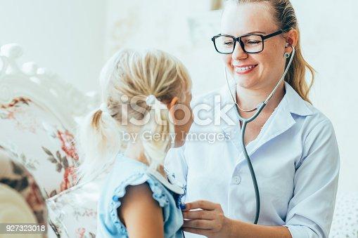 istock Smiling female doctor listening to little girl 927323018