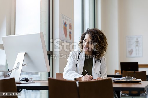 Sitting at her desk in her well lit office, the smiling mid adult female doctor makes notes for the upcoming consultation.