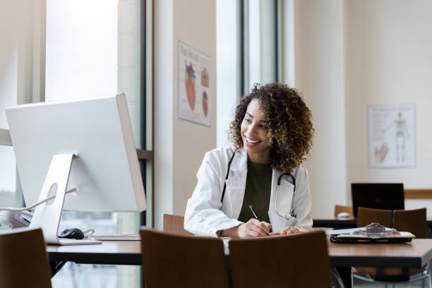 Smiling female doctor makes notes for upcoming consultation stock photo