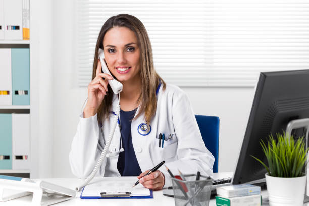 Smiling female Doctor sat at desk with telephone to ear – Foto