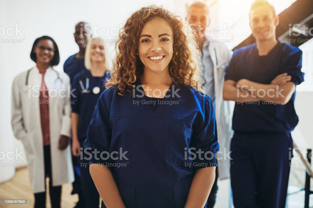 Smiling female doctor standing with medical colleagues in a hospital - Стоковые фото Близость роялти-фри