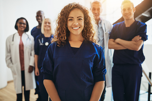 Smiling Female Doctor Standing With Medical Colleagues In A Hospital — стоковые фотографии и другие картинки Близость