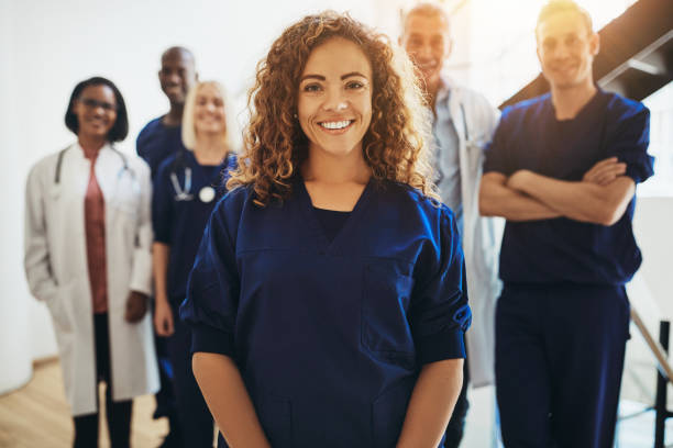Smiling female doctor standing with medical colleagues in a hospital Smiling young female doctor standing in a hospital corridor with a diverse group of medical staff standing behind her healthcare and medicine stock pictures, royalty-free photos & images