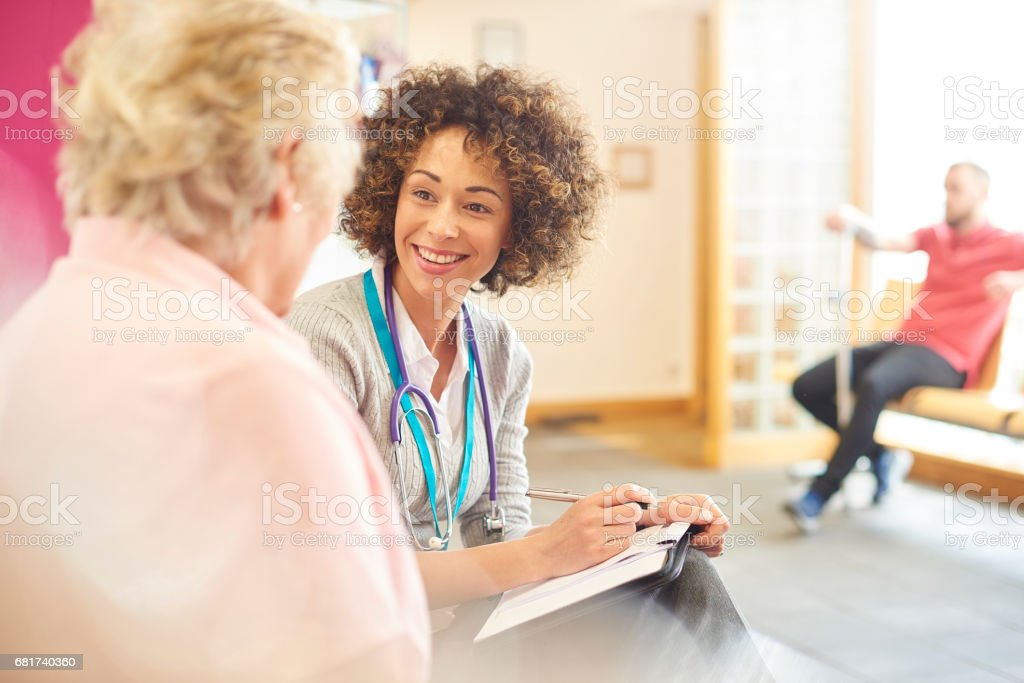 Smiling female doctor with senior patient stock photo
