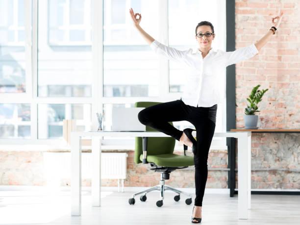 lächelnde frau turnen bei der arbeit - yoga fürs büro stock-fotos und bilder