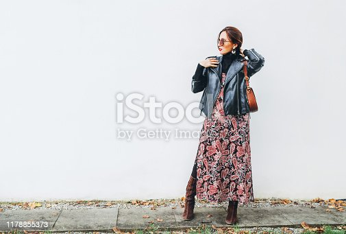 Smiling female dressed boho fashion style colorful long dress with black leather biker jacket with brown leather flap bag posing on the white wall background.