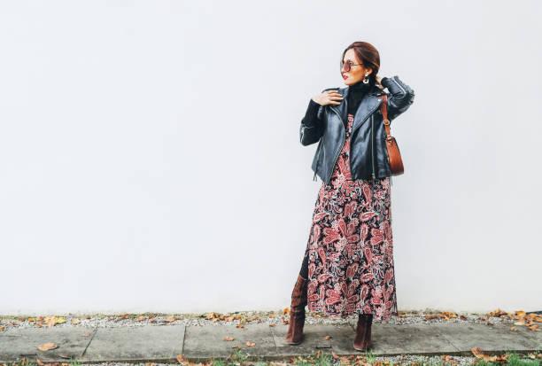 Sonriente mujer vestida boho estilo de moda colorido vestido largo con chaqueta biker de cuero negro con bolso de solapa de cuero marrón que posa sobre el fondo de la pared blanca. - foto de stock
